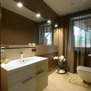 Diseño de aseo contemporáneo, de tamaño medio, con lavabo integrado, armarios con paneles lisos, sanitario de pared, baldosas y/o azulejos grises, baldosas y/o azulejos de porcelana, paredes marrones, suelo de baldosas de porcelana y puertas de armario amarillas