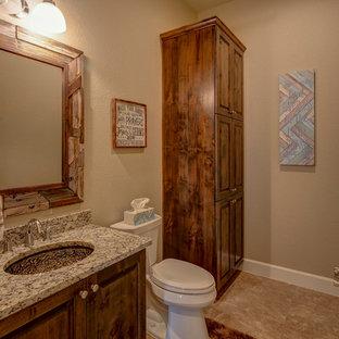 オースティンの大きいラスティックスタイルのおしゃれなトイレ・洗面所 (レイズドパネル扉のキャビネット、濃色木目調キャビネット、分離型トイレ、ベージュの壁、セラミックタイルの床、アンダーカウンター洗面器、御影石の洗面台、ベージュの床、マルチカラーの洗面カウンター) の写真