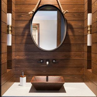 Immagine di un bagno di servizio costiero con ante con riquadro incassato, ante in legno bruno, pareti marroni, lavabo a bacinella e top bianco
