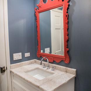 Réalisation d'un petit WC et toilettes marin avec des portes de placard blanches, un WC à poser, un carrelage gris, un mur bleu, un sol en galet, un lavabo encastré, un plan de toilette en quartz modifié et un placard avec porte à panneau encastré.