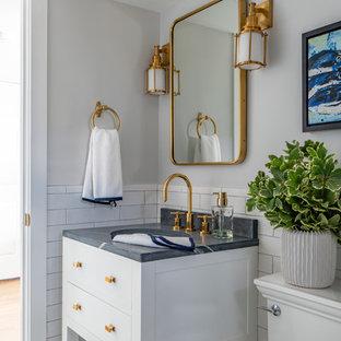 На фото: маленький туалет в морском стиле с фасадами островного типа, белыми фасадами, раздельным унитазом, белой плиткой, серыми стенами, врезной раковиной, мраморной столешницей, серой столешницей, плиткой кабанчик, полом из мозаичной плитки и белым полом с