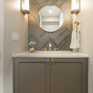 Design ideas for a small contemporary cloakroom in Seattle with shaker cabinets, grey cabinets, grey tiles, porcelain tiles, grey walls, light hardwood flooring, a submerged sink, solid surface worktops and beige floors.
