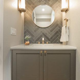 Cette photo montre un petit WC et toilettes tendance avec un placard à porte shaker, des portes de placard grises, un carrelage gris, des carreaux de porcelaine, un mur gris, un sol en bois clair, un lavabo encastré, un plan de toilette en surface solide et un sol beige.