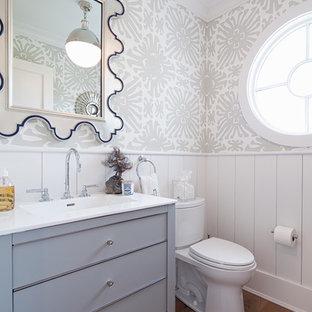 Idee per un bagno di servizio chic con ante lisce, ante grigie, WC a due pezzi, pareti grigie, parquet chiaro e lavabo da incasso