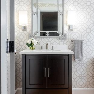Imagen de aseo clásico renovado, de tamaño medio, con puertas de armario negras, paredes grises, suelo de madera en tonos medios, lavabo bajoencimera, suelo marrón, encimeras blancas, armarios tipo mueble y encimera de cuarzo compacto