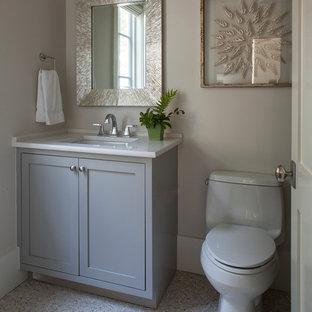 Aménagement d'un petit WC et toilettes bord de mer avec un placard à porte shaker, des portes de placard grises, un WC séparé, un carrelage beige, une plaque de galets, un mur gris, un sol en galet, un lavabo encastré et un plan de toilette en quartz modifié.