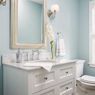 Ispirazione per un bagno di servizio chic di medie dimensioni con lavabo sottopiano, ante bianche, pareti blu, WC a due pezzi, lastra di pietra, parquet scuro, top in marmo, ante con riquadro incassato e top bianco
