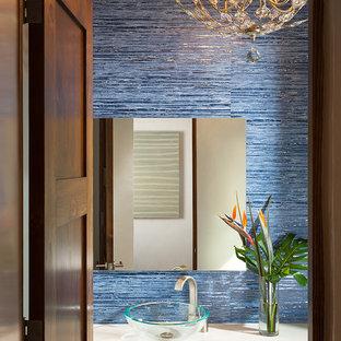 Modelo de aseo de estilo americano, pequeño, con lavabo sobreencimera, paredes azules, encimera de acrílico y baldosas y/o azulejos azules