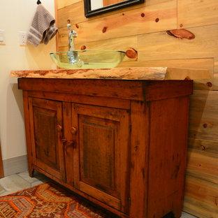デンバーの中サイズのラスティックスタイルのおしゃれなトイレ・洗面所 (シェーカースタイル扉のキャビネット、中間色木目調キャビネット、一体型トイレ、ベージュのタイル、セラミックタイル、白い壁、ライムストーンの床、ベッセル式洗面器、木製洗面台、マルチカラーの床、ブラウンの洗面カウンター) の写真
