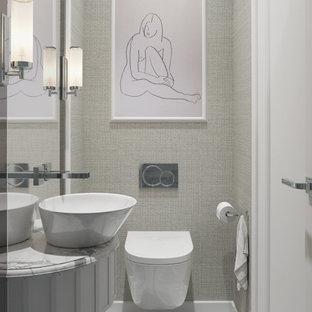 Inspiration pour un petit WC et toilettes minimaliste avec un placard en trompe-l'oeil, des portes de placard beiges, un WC suspendu, un carrelage noir et blanc, des carreaux de céramique, un mur beige, un sol en carrelage de céramique, une vasque et un plan de toilette en marbre.