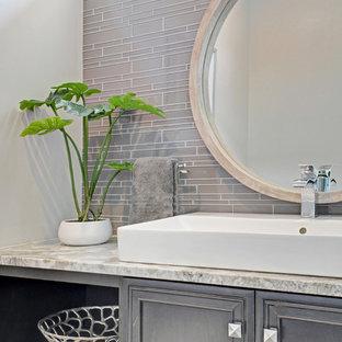 Идея дизайна: туалет среднего размера в стиле современная классика с фасадами островного типа, коричневыми фасадами, раздельным унитазом, серой плиткой, стеклянной плиткой, серыми стенами, полом из керамической плитки, раковиной с несколькими смесителями, столешницей из искусственного кварца, серым полом и бежевой столешницей