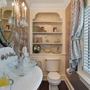 Cette photo montre un petit WC et toilettes tendance avec un placard à porte plane, des portes de placard en bois sombre, un WC à poser, un sol en bois foncé, une vasque, un plan de toilette en marbre, un mur marron, un sol marron, un carrelage gris et carrelage en métal.