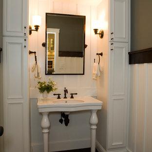 Imagen de aseo de estilo americano con puertas de armario blancas y lavabo tipo consola