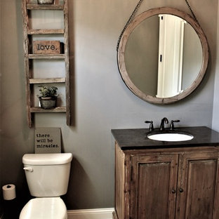 Design ideas for a small rustic cloakroom in Chicago with raised-panel cabinets, grey walls, a submerged sink, dark wood cabinets, a two-piece toilet, light hardwood flooring, solid surface worktops and brown floors.