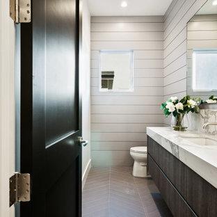 Cette photo montre un WC et toilettes nature de taille moyenne avec des portes de placard en bois sombre, un mur gris, un lavabo encastré, un plan de toilette en marbre, un plan de toilette multicolore, meuble-lavabo suspendu et du lambris.