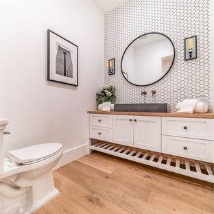 他の地域の小さいコンテンポラリースタイルのおしゃれなトイレ・洗面所 (シェーカースタイル扉のキャビネット、白いキャビネット、一体型トイレ、白いタイル、セラミックタイル、白い壁、木製洗面台、オレンジの洗面カウンター) の写真