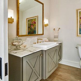 Idee per un bagno di servizio tradizionale con ante grigie, pareti grigie, pavimento in legno massello medio, lavabo da incasso, pavimento marrone e top bianco