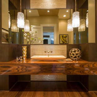 Inspiration for a large contemporary beige tile medium tone wood floor powder room remodel in DC Metro with a vessel sink, flat-panel cabinets, medium tone wood cabinets, wood countertops, beige walls and brown countertops
