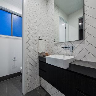 Exemple d'un petit WC et toilettes tendance avec un placard à porte plane, des portes de placard en bois sombre, un WC séparé, un carrelage blanc, des carreaux de céramique, un mur blanc, un sol en carrelage de céramique, une grande vasque, un plan de toilette en granite et un sol gris.