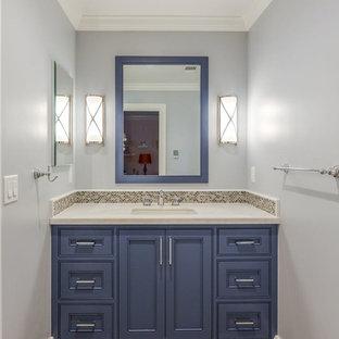 Пример оригинального дизайна: туалет среднего размера в стиле современная классика с унитазом-моноблоком, плиткой из листового стекла, врезной раковиной, бежевым полом, фасадами с утопленной филенкой, коричневыми фасадами, бежевой плиткой, мраморной столешницей, синими стенами и бежевой столешницей