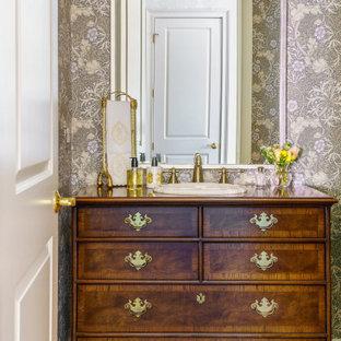 Réalisation d'un WC et toilettes tradition avec un placard à porte plane, des portes de placard en bois brun, un mur gris, un sol en bois brun, un lavabo posé, un plan de toilette en bois, un sol marron, un plan de toilette marron, meuble-lavabo sur pied et du papier peint.