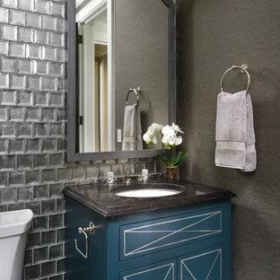 Esempio di un bagno di servizio chic con consolle stile comò, ante blu, WC a due pezzi, piastrelle grigie, piastrelle di vetro, pareti grigie e lavabo sottopiano