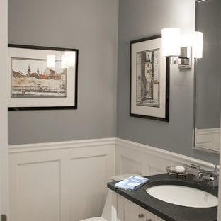 ニューヨークのトラディショナルスタイルのおしゃれなトイレ・洗面所 (アンダーカウンター洗面器、シェーカースタイル扉のキャビネット、白いキャビネット、ソープストーンの洗面台、一体型トイレ、グレーの洗面カウンター) の写真