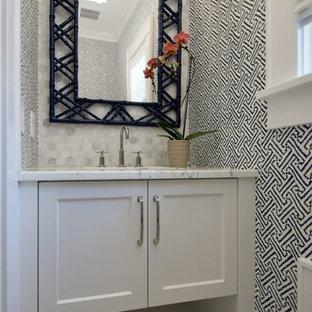 Réalisation d'un petit WC et toilettes tradition avec des portes de placard blanches, un carrelage blanc, des carreaux de porcelaine, un mur multicolore, un sol en marbre, un lavabo encastré, un plan de toilette en marbre, un plan de toilette blanc et un placard à porte shaker.