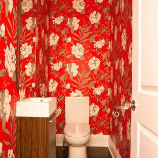 Cette image montre un petit WC et toilettes traditionnel avec un placard à porte plane, des portes de placard en bois sombre, un mur rouge, un sol en bois foncé et un lavabo suspendu.