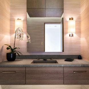 Exemple d'un WC et toilettes tendance avec un placard à porte plane, des portes de placard en bois sombre, un mur marron, un lavabo intégré et un plan de toilette gris.