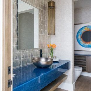 オレンジカウンティの広い地中海スタイルのおしゃれなトイレ・洗面所 (オープンシェルフ、中間色木目調キャビネット、ベージュのタイル、ベージュの壁、無垢フローリング、ベッセル式洗面器、茶色い床、青い洗面カウンター) の写真