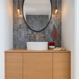 デンバーの小さいコンテンポラリースタイルのおしゃれなトイレ・洗面所 (フラットパネル扉のキャビネット、淡色木目調キャビネット、一体型トイレ、マルチカラーのタイル、大理石タイル、白い壁、淡色無垢フローリング、ベッセル式洗面器、木製洗面台、ベージュの床、ブラウンの洗面カウンター、フローティング洗面台) の写真