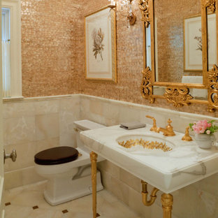 Powder room - mid-sized traditional marble tile beige floor and marble floor powder room idea in Boston with a one-piece toilet, multicolored walls, a console sink and marble countertops