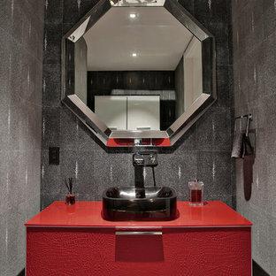 Cette image montre un grand WC et toilettes design avec un lavabo encastré, un placard à porte plane, des portes de placard rouges, un carrelage gris, un mur gris et un sol en carrelage de porcelaine.
