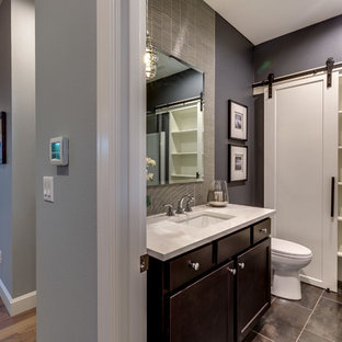 Design ideas for a medium sized traditional cloakroom in Portland with shaker cabinets, dark wood cabinets, a two-piece toilet, multi-coloured tiles, glass tiles, grey walls, ceramic flooring, a submerged sink, engineered stone worktops and black floors.