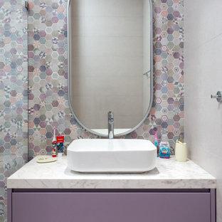 Imagen de aseo actual, de tamaño medio, con armarios con paneles lisos, puertas de armario violetas, baldosas y/o azulejos en mosaico, paredes blancas, lavabo sobreencimera y encimeras blancas