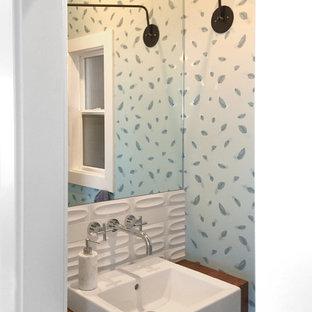 Modelo de aseo actual con armarios abiertos, puertas de armario de madera oscura, sanitario de dos piezas, baldosas y/o azulejos blancos, paredes verdes, suelo de madera clara y lavabo sobreencimera