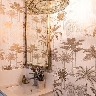 Ispirazione per un piccolo bagno di servizio tropicale con ante bianche, pareti bianche, lavabo da incasso e top in quarzo composito