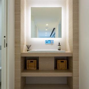 Пример оригинального дизайна: маленький туалет в стиле модернизм с накладной раковиной, открытыми фасадами, светлыми деревянными фасадами, столешницей из ламината, керамогранитной плиткой, белыми стенами, полом из керамогранита и бежевой плиткой