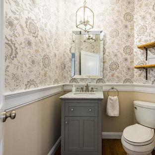 Idée de décoration pour un petit WC et toilettes tradition avec des portes de placard grises, un mur multicolore, un sol en bois brun, un lavabo encastré, un WC séparé et un placard avec porte à panneau encastré.