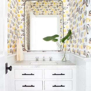 Inspiration pour un WC et toilettes marin de taille moyenne avec un placard en trompe-l'oeil, des portes de placard blanches, un mur multicolore, un lavabo encastré, un plan de toilette blanc, un WC à poser et un plan de toilette en marbre.