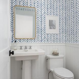 Cette photo montre un petit WC et toilettes nature avec des portes de placard blanches, un WC à poser, un mur blanc, un sol en bois brun, un lavabo de ferme, un sol marron, meuble-lavabo sur pied et du papier peint.