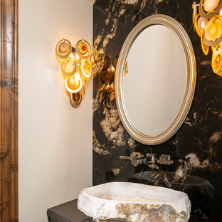 Idées déco pour un WC et toilettes sud-ouest américain avec un placard à porte plane, des portes de placard marrons, un carrelage multicolore, un mur beige, une vasque et un plan de toilette marron.