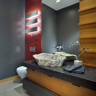 Cette image montre un grand WC et toilettes design avec une vasque, un placard à porte plane, des portes de placard en bois brun, un carrelage rouge, un mur gris, un plan de toilette en quartz, un WC suspendu, des carreaux de céramique, un sol en carrelage de porcelaine et un plan de toilette gris.