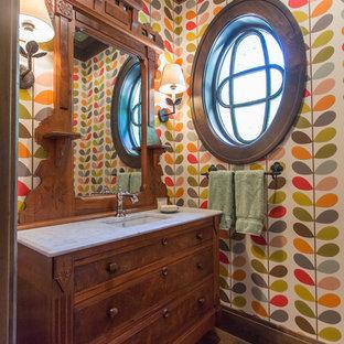Diseño de aseo de estilo americano con puertas de armario marrones, baldosas y/o azulejos multicolor, paredes multicolor, suelo de madera en tonos medios, lavabo integrado y suelo marrón