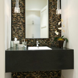 This is an example of a contemporary cloakroom in Dallas with a built-in sink, pebble tiles and grey tiles.