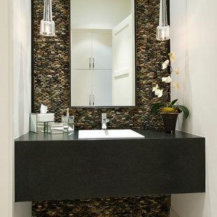 Cette photo montre un WC et toilettes tendance avec un lavabo posé, une plaque de galets et un carrelage gris.