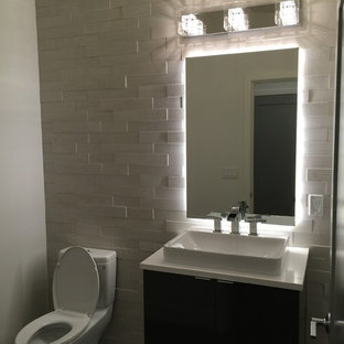 Photo of a small modern cloakroom in Seattle with flat-panel cabinets, dark wood cabinets, a one-piece toilet, white tiles, stone tiles, white walls, a vessel sink and quartz worktops.