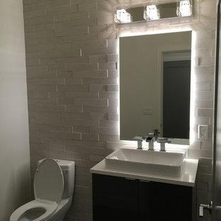 Cette photo montre un petit WC et toilettes moderne avec un placard à porte plane, des portes de placard en bois sombre, un WC à poser, un carrelage blanc, un carrelage de pierre, un mur blanc, une vasque et un plan de toilette en quartz.