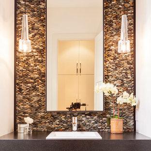Imagen de aseo actual con lavabo encastrado, suelo de baldosas tipo guijarro y encimeras grises